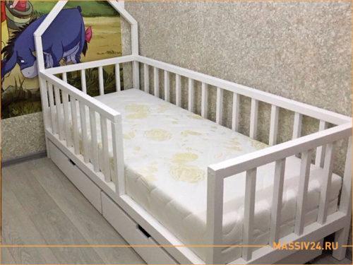 Белая кроватка с ограждением и выдвижными ящиками