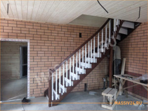 Красивая белая и коричневая лестница в кирпичном коттедже из массива дерева